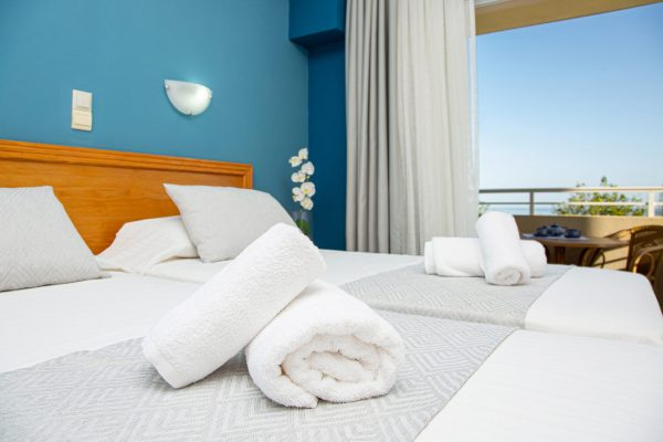 Superior Triple Studios with Sea View or Garden View bed detail and balcony view